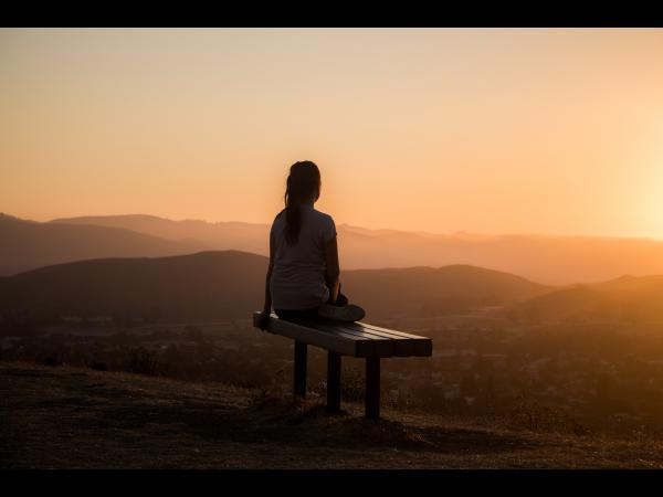 Woman sitting on bench at sunset